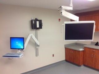 Wall mounted computer workstation and ceiling mounted monitor improve efficiency in a healthcare setting